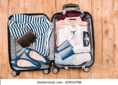 Overhead view of traveler's accessories and clothes organized in open luggage on wooden floor