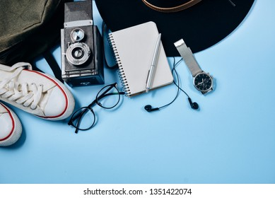 Overhead view of Traveler's accessories on blue background with retro camera, hat, backpack, eyeglasses, clock, pen, passport, shoes and notepad. Flat lay, top view. Summer background.