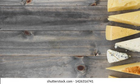 An overhead view of triangular cheese wedges on wooden table