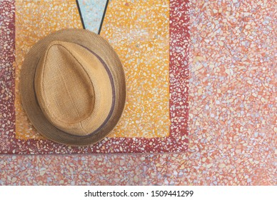 Overhead view of Trilby straw hat laying on top of Mediterranean style Terrazzo stone bench and floor - Aerial shot of a mens hat on  stylish summer alfresco outdoor patio - Trendy and fashion concept