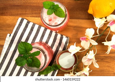 overhead view of two mason jars on a wood table with a pink vodka cocktail with a mint leaf and flowers by a white brick wall with lime wedges