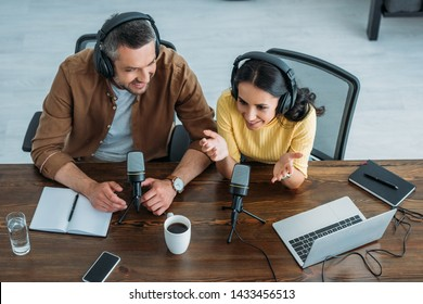 overhead view of two smiling radio hosts recording podcast in radio studio