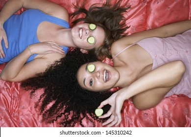 Overhead view of two teenage girls lying pink sheet with cucumbers over eyes