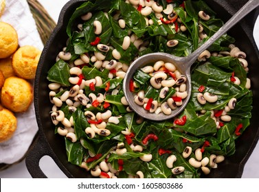 Overhead view of US southern dish of black-eye peas and collard greens with corn bread on the side