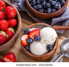 Overhead view of vanilla ice cream with fresh blueberries and strawberries in a wooden bowl