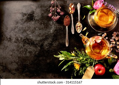 Overhead view of various sorts of tea. Flavoured with Assorted Herbs, an apple, rose with a teapot and a teacup on a rustic black metal board