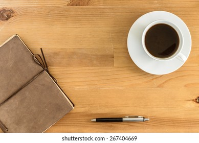 Overhead view of a vintage leather notebook, pen, and cup of coffee on a rustic wood table.