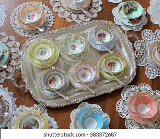 overhead view of vintage tea cup sets on a silver tray with lace doily and silver teaspoons