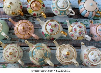 Overhead view of vintage teapots on a rustic distressed wood table