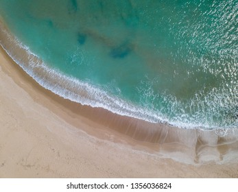 Overhead view of waves breaking on the shore at the beach in Cullera, Valencia, Spain