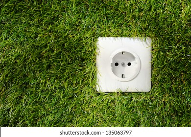 Overhead view of a white plastic outdoor electrical power socket embedded in green grass with copyspace alongside