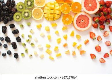Overhead view of whole fruits and cut slices in the rows, red, orange, yellow, green fruits with cut pieces on the white background, grapefruit, mango, strawberries, orange, lemon, kiwi
