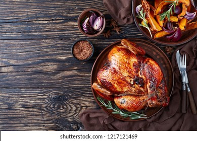 overhead view of a whole roasted chicken with golden brown crispy skin served on a earthenware dish with caramelized grilled pumpkin slices and grilled onion, view from above, flat lay, copy space