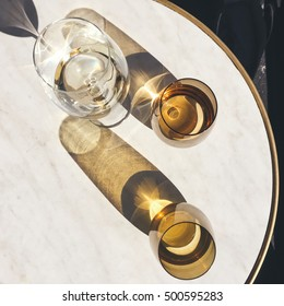 Overhead view of wine glass and water on a marble cafe table in the sun