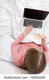 overhead view of woman with laptop and coffee sitting in bed