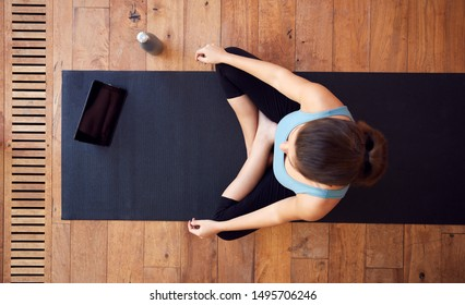 Overhead View Of Woman Sitting On Exercise Mat Using Digital Tablet