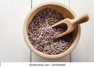 Overhead view of a wooden bowl and scoop, filled with dried lavender herb flower buds.