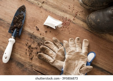 Overhead view of wooden floor strewn with gardening gloves and spilled seeds beside black boots and a trowel