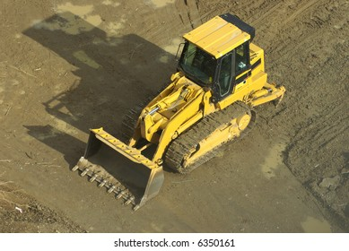 Overhead view of a yellow front end loader (bulldozer type machine) on a construction site