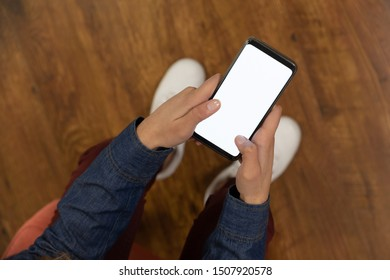Overhead view of a young Caucasian man standing at home holding a smartphone