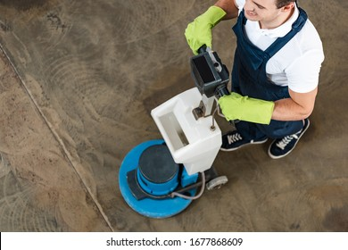 overhead view of young cleaner cleaning floor in office