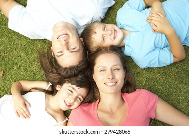 Overhead View Of Young Family Lying On Grass In Park