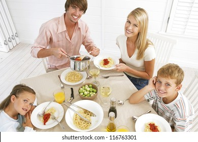 Overhead view of a young family sitting at the dining table eating spaghetti bolognaise