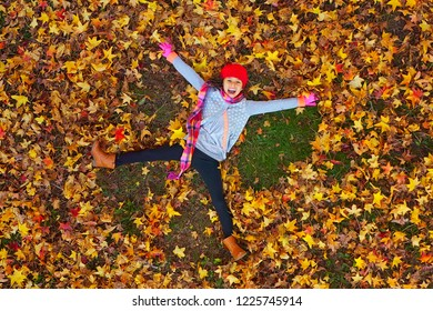 Overhead view of a Young girl making leaf angels in autumn foliage