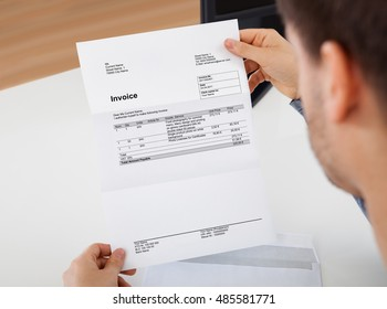 Overhead view of young man reading a invoice document