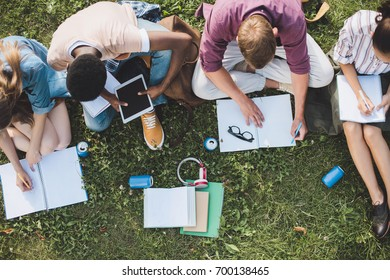 overhead view of young multiethnic students studying and digital tablet while sitting together on grass