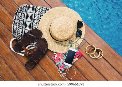 Overhead  view of young woman  holidays summer accessories on wood background, near pool. With copy space. Straw hat, mobile phone with earphones, notebook , boho stylish bag and  leather sandals.