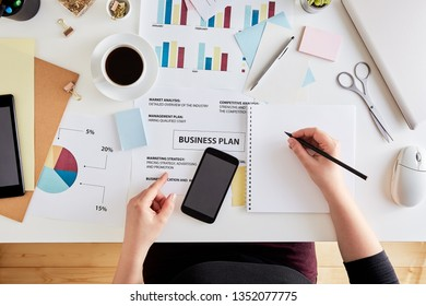 Overhead view of young woman planning business strategy. Desk of a modern businesswoman