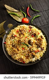overhead  view-Delicious homemade mutton or lamb dum biriyani over wooden background,