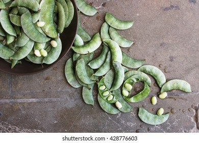 Overhead of whole, raw, green bean pods in a bowl and scattered with beans