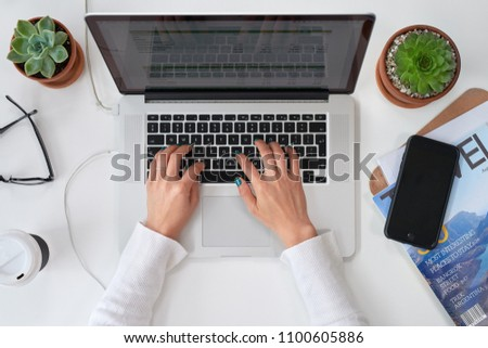 Overhead of work desk with woman typing replying to emails on laptop computer, freelance entrepreneur creative