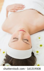 Overhead of a young beautiful woman with eyes closed lying on massage table in beauty salon