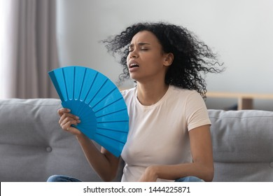 Overheated african young woman feeling hot waving fan annoyed with high temperature sit on sofa at home, stressed black girl sweating suffer from summer weather heat problem without air conditioner