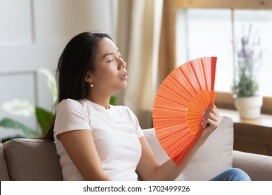 Overheated asian woman sweating feels discomfort seated on sofa at home without air-conditioning system. Tired girl suffers from heat stroke waving orange color fan cools herself in hot summer weather