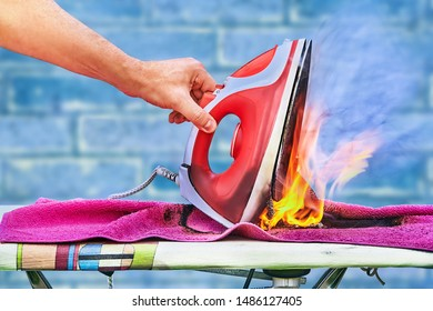 An overheated clothes iron ignited on an ironing board, a fire started in the house, a hand raises a charred iron. The plastic melted, the linen burned.