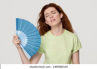 Overheated redhead woman sweating feel uncomfortable suffer from heat stroke perspiration problem, tired sweaty lady waving fan cooling in hot summer weather isolated on white grey studio background