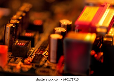 Overheated Transistor on Computer Board in Red and Gold Coolors