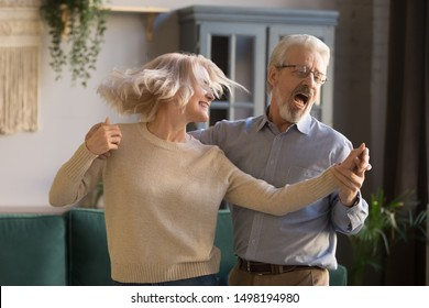 Overjoyed active retired mature couple dancing together enjoy leisure activity in living room, happy cheerful senior grey-haired husband and wife feel excited have fun relaxing on weekend at home