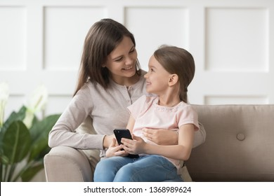 Overjoyed adorable daughter holds smart phone sitting on mothers lap looking at each other feels happy. Modern tech usage, bad habit kids and electronic gadgets, parental control online safety concept