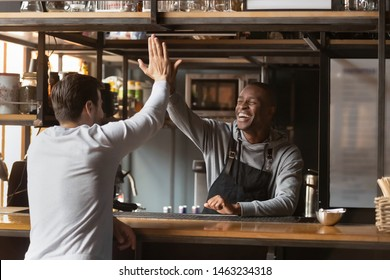Overjoyed african American barista give high five celebrating successful business cafe option with manager, excited black waiter greeting friend at bar or cafe, join hands having fun with client