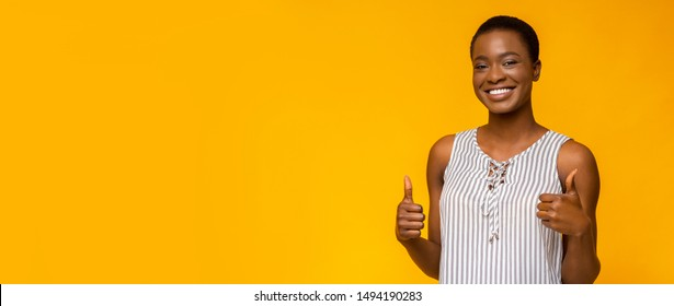 Overjoyed african american girl showing thumbs up to free space, widely smiling, yellow studio background