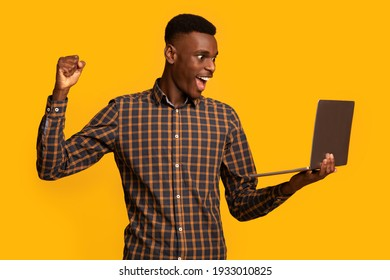 Overjoyed African American male with laptop in hands celebrating online win, lucky happy black young guy raising hand and exclaiming with joy, standing isolated over yellow background, free space