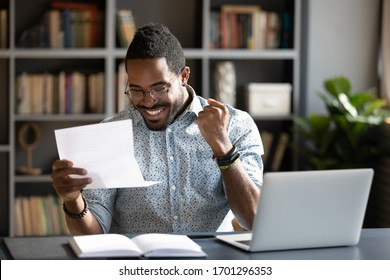 Overjoyed African American male student feel euphoric read good news in paperwork letter, excited biracial man triumph get positive answer reply in paper postal correspondence, success concept