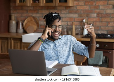 Overjoyed African American man talking on phone, distracted from work or studying, sitting at table with laptop at home, chatting with friends during break, hearing good news, pleasant conversation