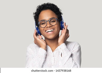 Overjoyed african American millennial woman in glasses isolated on grey studio background enjoy music in blue Bluetooth headphones, happy black girl in earphones smile listen to tracks or radio