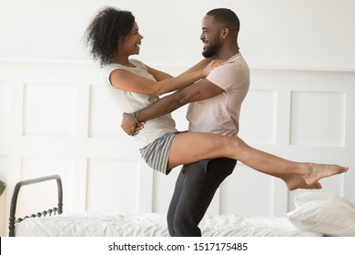 Overjoyed african couple spend time in bedroom, american boyfriend holds beloved girlfriend in his arms stand near bed, lovers in nightwear enjoy romantic date together intimacy closeness love concept